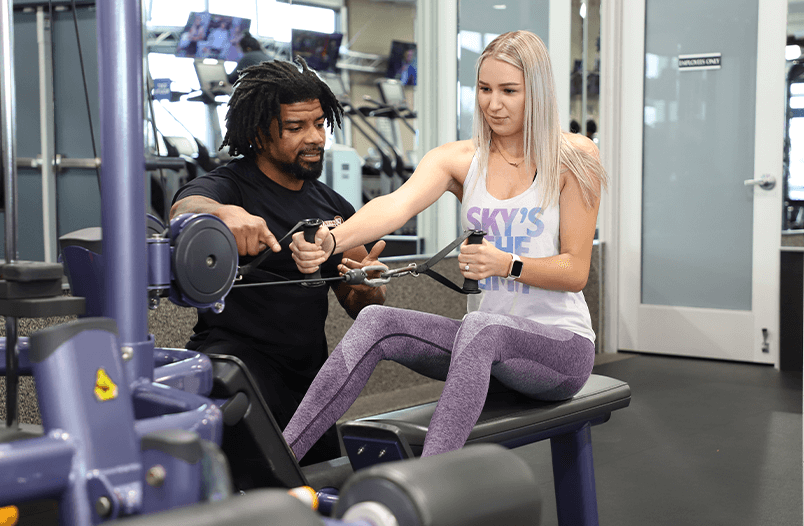 Personal Trainer showing a client how to use a row machine