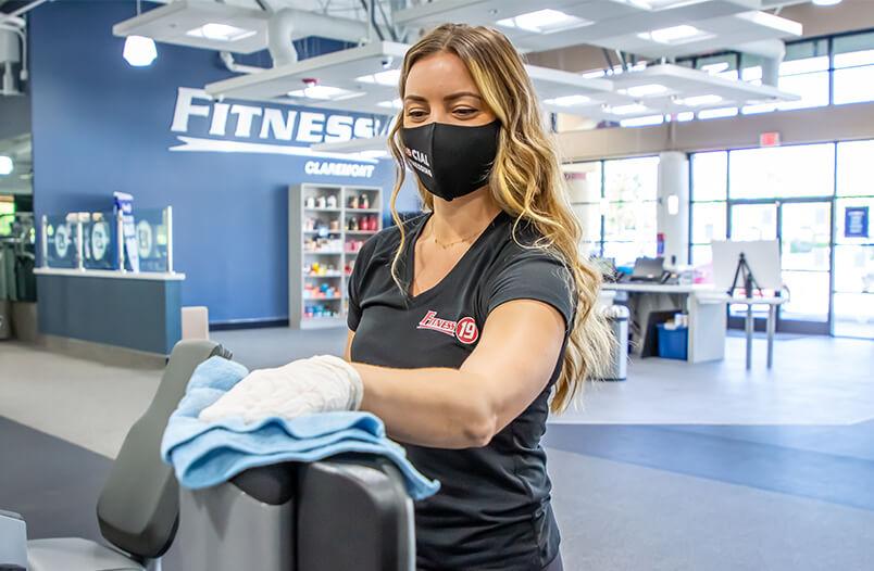Fitness 19 team member cleaning equipment